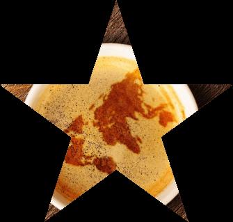 Foto ilustrativa de uma xícara de café com um mapa mundi desenhado